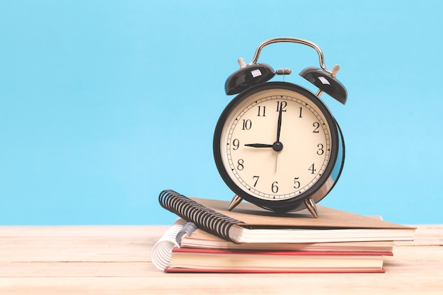 A pile of books and alarm clock on a wooden with blue background