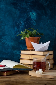 Pile of books, a cup of hot tea, a paper boat, an open diary with a pen on a dark blue wall