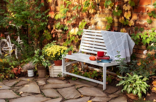 Pile of books, cup of tea, plaid and pumpkin lie on wooden bench in garden. decor autumn yard