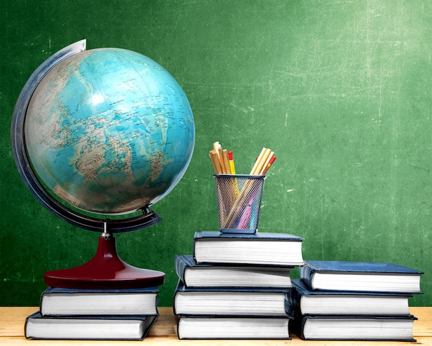 Pile of books and globe with pencils in basket container on wooden table