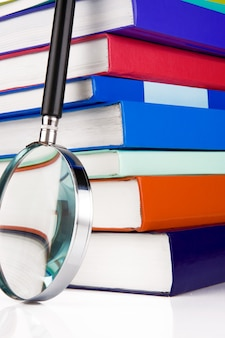 Pile of books and magnifying glass isolated on white