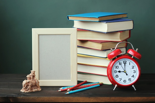 Pile of books, red alarm clock, frame for a photo and colored pencils