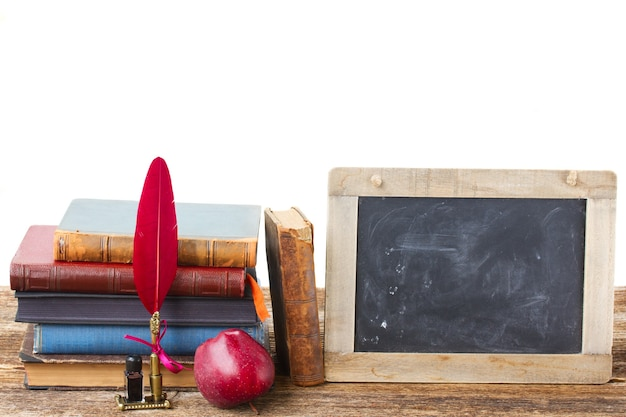 Pile of books and red feather pen  with empty blackboard isolated on white
