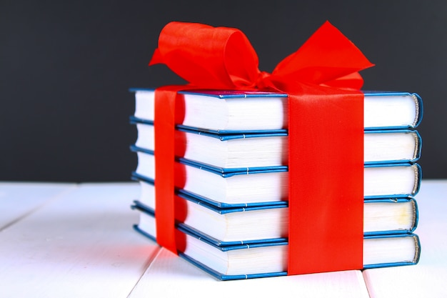 A pile of books tied with a red ribbon on a white wooden table. gift on background of a chalkboard