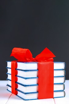 A pile of books tied with a red ribbon on a white wooden table.