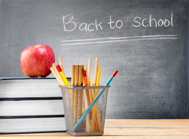 Pile of books with apple and pencils in basket container on wooden table and blackboard with back to school message