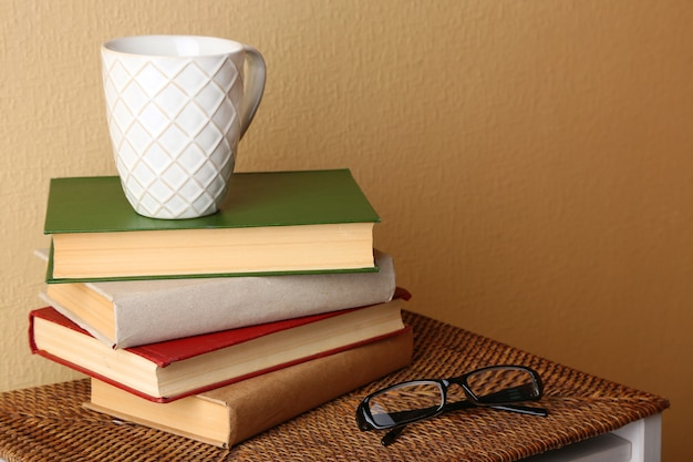 Pile of books with cup and glasses on wicker surface and light wall