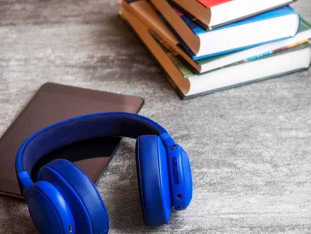 Pile of books with headphones on the table