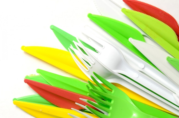 Pile of bright yellow, green and white plastic kitchenware single use appliances
