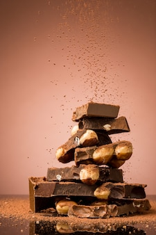 Mucchio di cioccolato rotto sulla tavola contro il fondo marrone dello studio