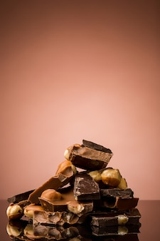 Pile of broken chocolate on table against brown studio background