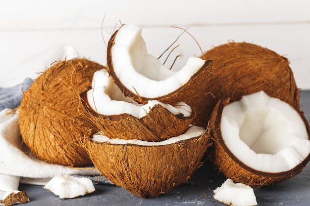 Pile of broken coconuts on ripped grey background