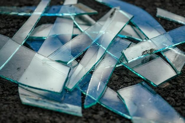 A pile of broken glass lying on the asphalt