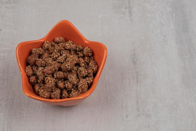 Mucchio di caramelle con semi di sesamo in una ciotola arancione.