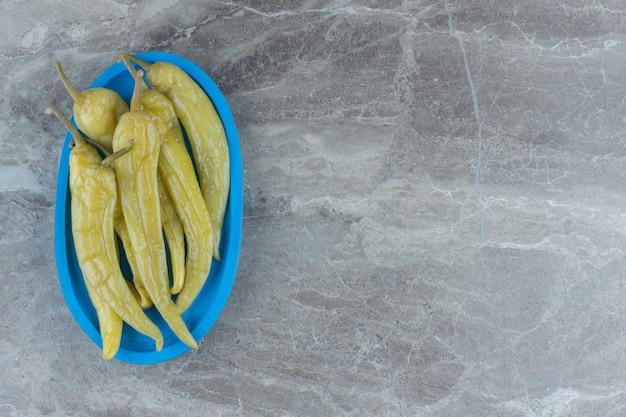 Mucchio di peperoncino verde inscatolato sul piatto di legno.