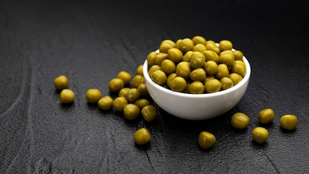 Pile of canned green peas in bowl on black