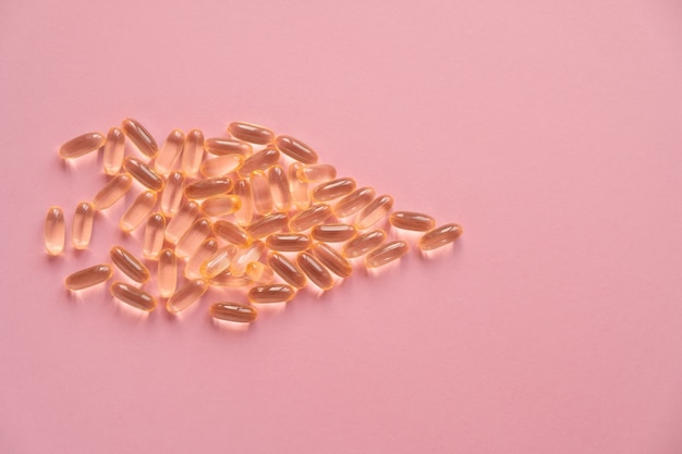 Pile of capsules omega 3 on pink background. close up, top view, high resolution product.