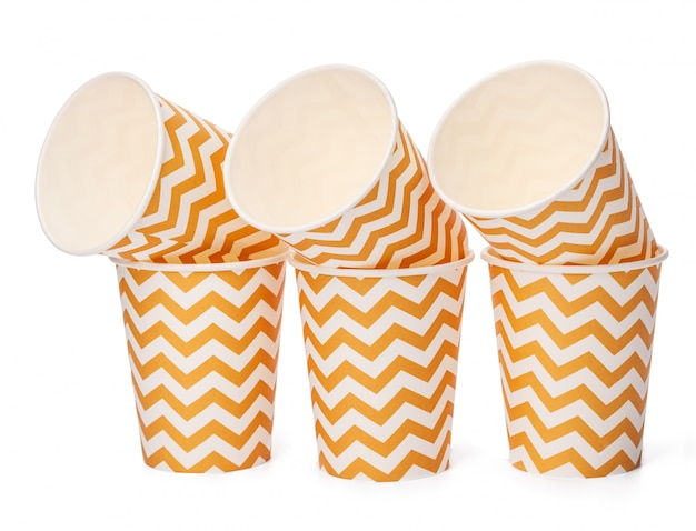 Pile of cardboard cups with beige geometric pattern isolated on white background