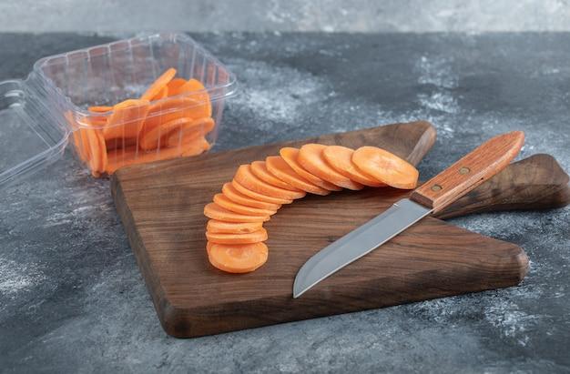 Mucchio di fette di carota su tavola di legno e all'interno di un contenitore di plastica.