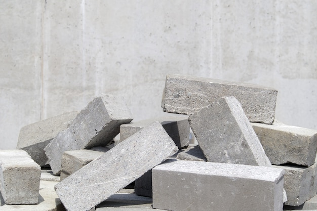 A pile of cement type bricks. solid brick is used for construction. lots of loose concrete bricks at the construction site.