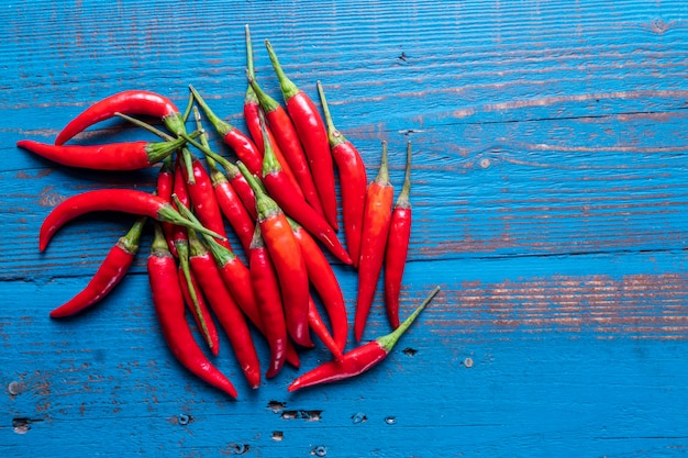 Pile of chili hot peppers on blue wooden background