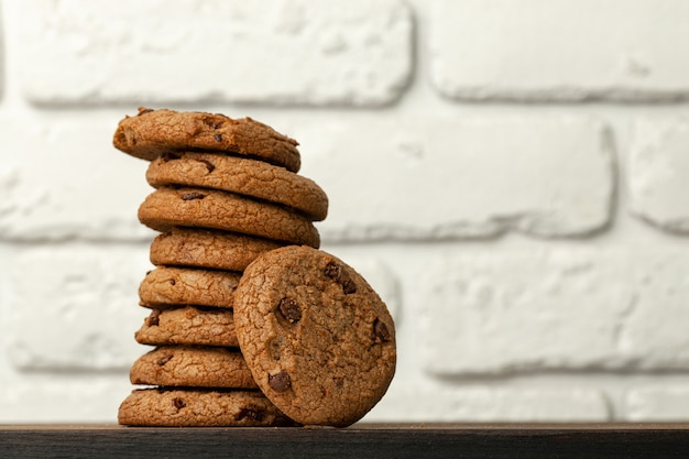 Pile of chocolate chip cookies against white brick wall
