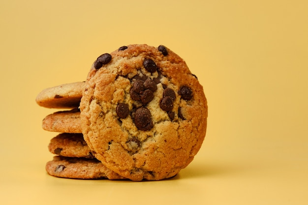 Pile of chocolate chip cookies on yellow backgreound front view