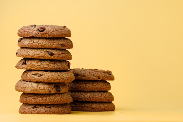 Pile of chocolate chip cookies on yellow backgreound
