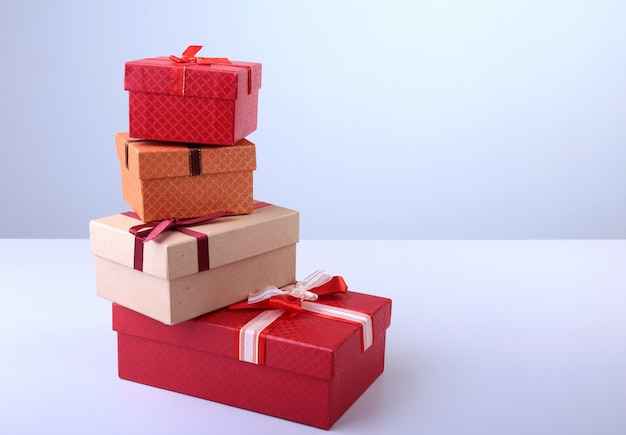 A pile of christmas gifts in colorful wrapping with ribbons on a beautiful hardwood floor with copyspace