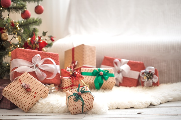 Pile of christmas presents over light wall on wooden table with cozy rug. christmas decorations