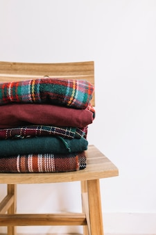 Pile of christmas sweaters on wooden chair