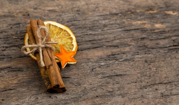 A pile of cinnamon sticks, dried orange and tangerine stars on old wooden table with copy space. christmas decoration. christmas card