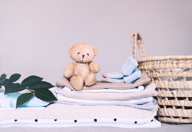 Pile of clean baby clothes skin care cosmetic teddy bear toy and laundry basket for newborn