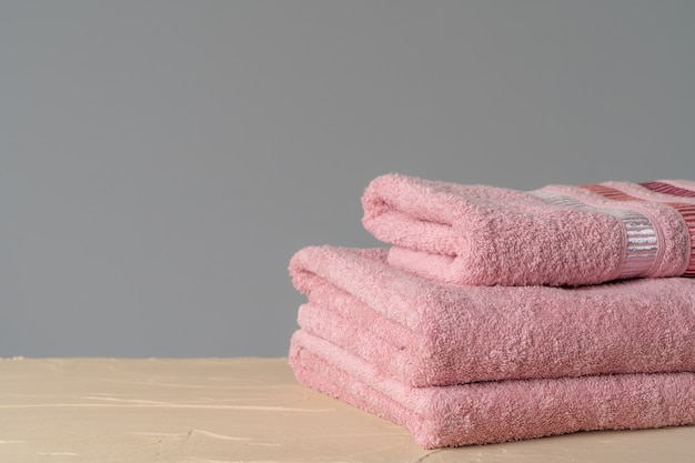 Pile of clean new towels against grey wall