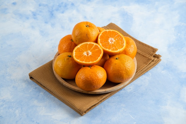 Pila di clementine mandarin n piatto di legno sopra l'asciugamano