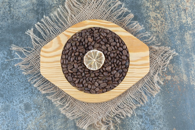 Pile of coffee beans and lemon slice on wooden plate.