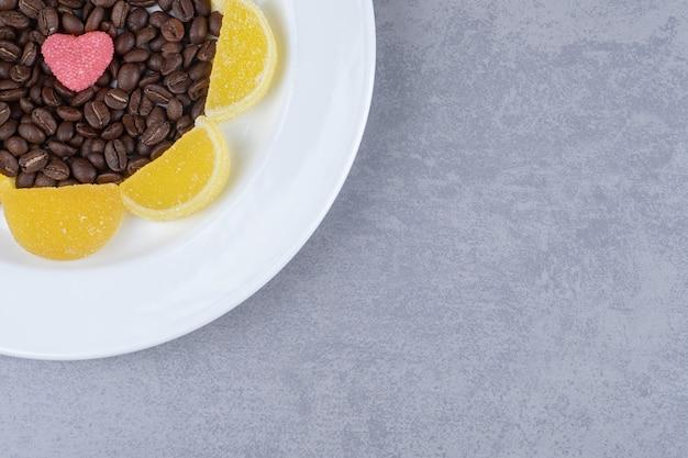 Pila di chicchi di caffè e marmellate su un piatto sulla superficie in marmo
