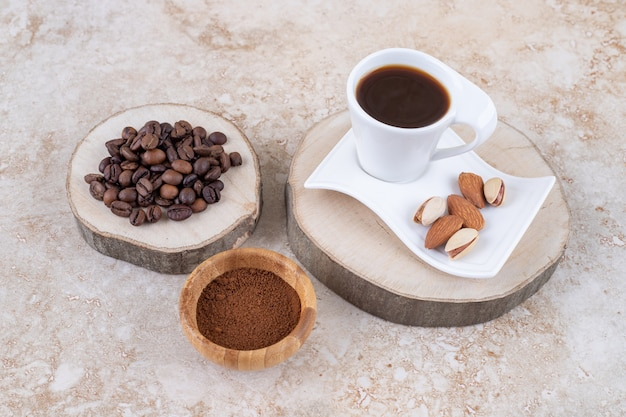 Pile of coffee beans on a wooden board next to a small bowl of ground coffee and a cup of coffee with almonds and pistachios