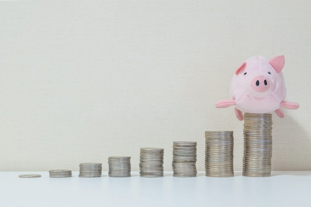 Pile of coin start from low to high with pig doll on the top in success of saving money concept