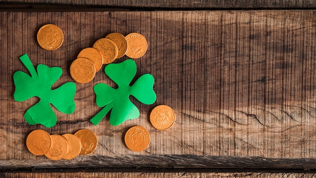 Pile of coins and paper shamrocks on wooden table