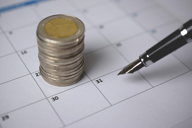 A pile of coins and a pen on the calendar.