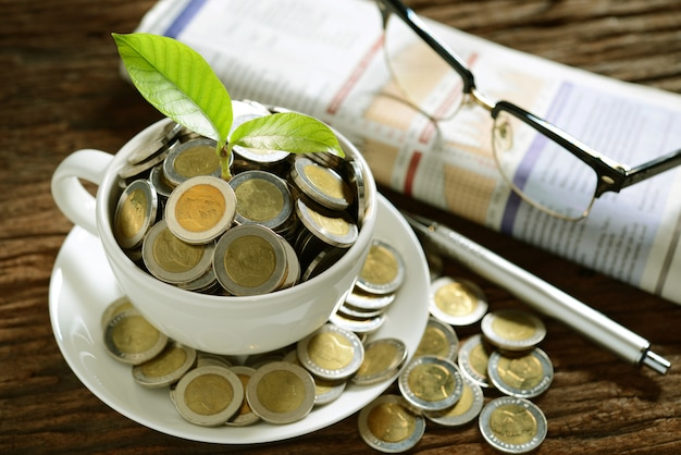 Pile of coins and young plant on top in coffee cup with newspapers and glasses