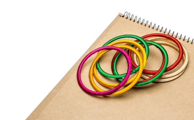 A pile of colorful bobbin bangles above a wooden textured notebook on white background with copy space