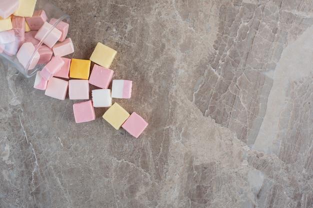 Mucchio di caramelle colorate su sfondo grigio.