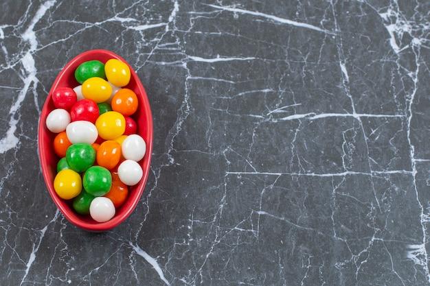 Pila di caramelle colorate in ciotola rossa.