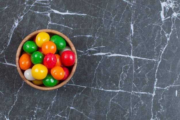 Pila di caramelle colorate nella ciotola di legno
