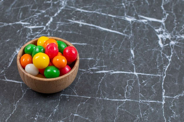 Pile of colorful candies in wooden bowl.