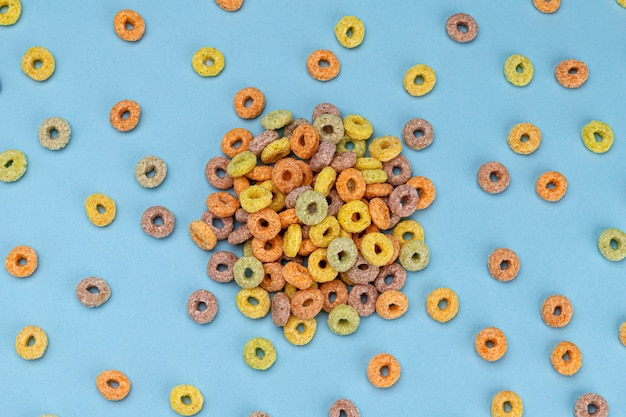 Pile of colorful corn rings on blue background, top view