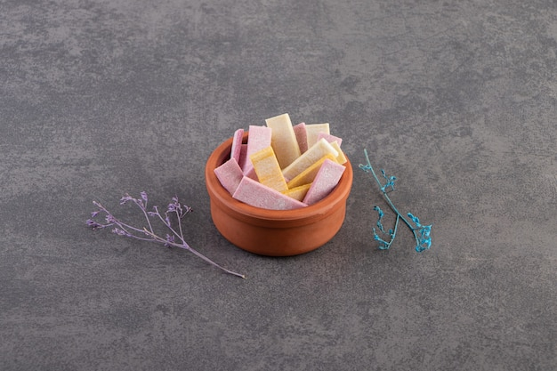 Pile of colorful gums in pottery bowl over grey background.