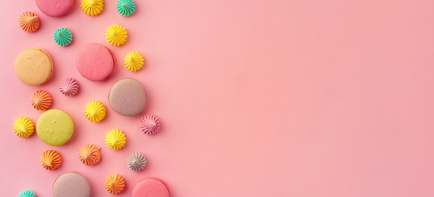 Pile of colorful macaroon cookies on pink, banner background, flat lay